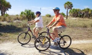Senior couple riding bikes at the beach